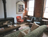 Sit on a big comfy sofa by the fire in the lounge