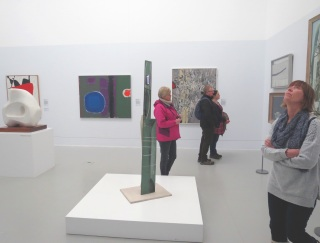 Gallery One - Far left: Roger Hilton 'February 1954' (1954) Far left: Dame Barbara Hepworth 'Image II' (1960) Left: Patrick Heron 'Green and Purple Painting with Blue Disc' (1960) Right: Bryan Wynter 'Riverbed' (1959)